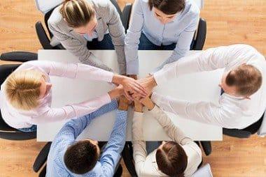 Equipo de personas juntan sus manos